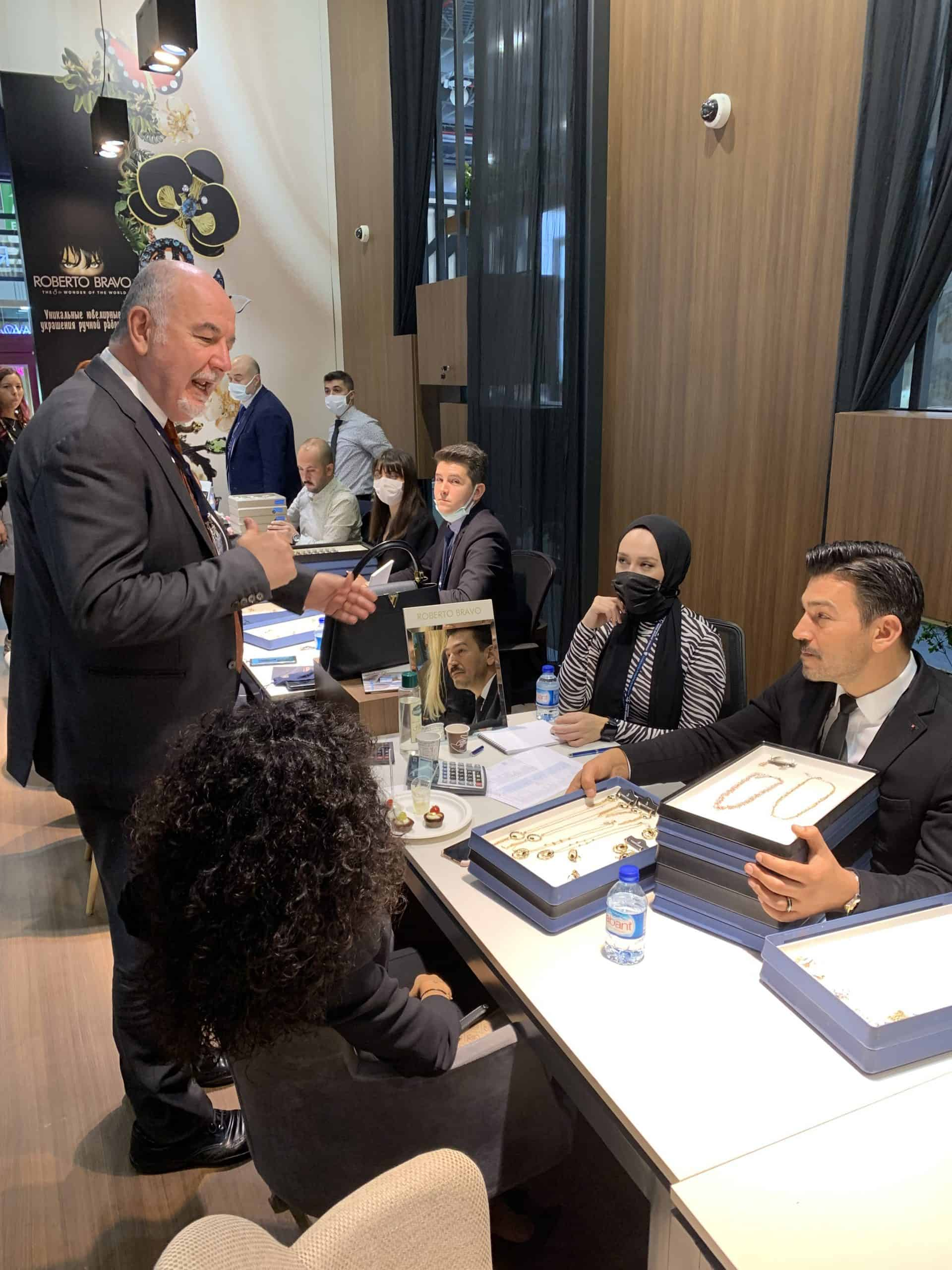 Roberto Bravo CEO Mustafa Kamar speaks with a staff member at the brand's stand at the Istanbul Jewelry Show
